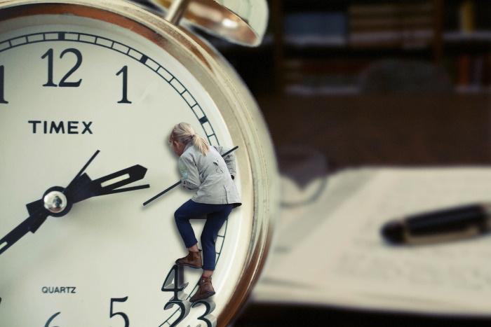 woman holding clock hands